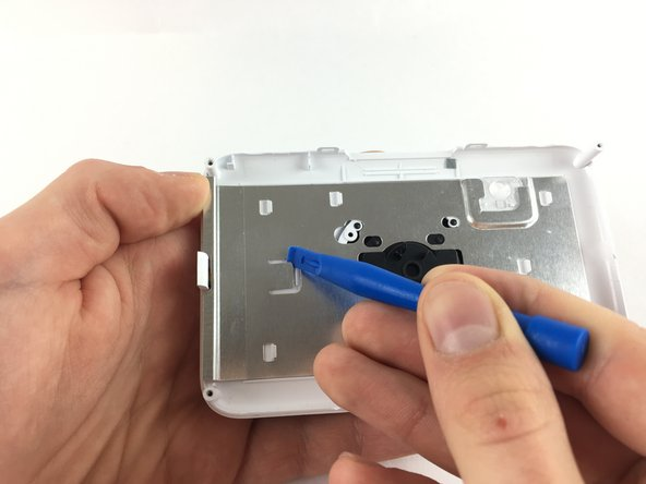 Use a plastic opening tool and pull up on the small metal tab in the middle-left inside of the front face-plate.