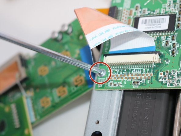 Remove the flanged Philips screw from the circuit board, located just under the large data ribbon connecting both boards.