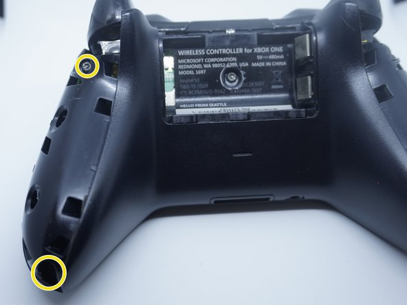 Remove the screw under the battery cover label. To do this, puncture a hole in the battery compartment where the photo is marked. It is located roughly in the center of the battery bay where it is marked on my controller.