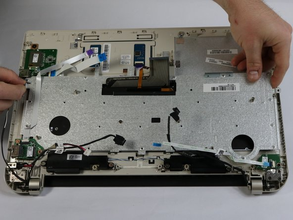 Carefully lift the keyboard retaining plate away from the laptop making sure not to damage any connectors.