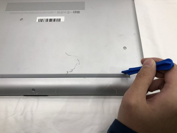 Using the plastic opening tools, peel back the plastic feet from the underside of the laptop.