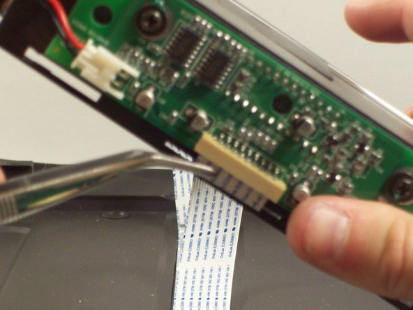 Grab onto ribbon cable with tweezers and gently pull until it come outs.