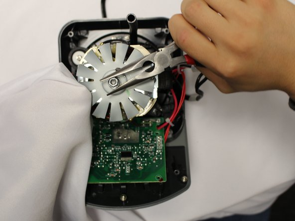 Use a wrench or a pair of pliers to help remove the nut on top of the fan. Holding the fan itself will help make the process easier.