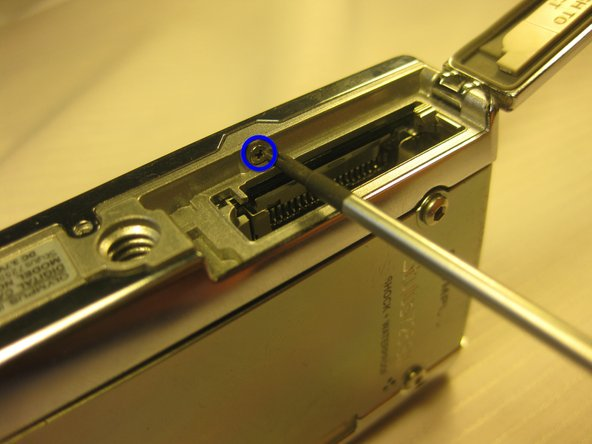 Unscrew the 2mm long screws securing the sides of the camera which holds the back panel. Use the same screwdriver.