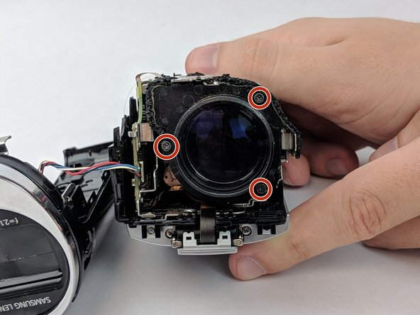Locate and remove the three 4mm Phillips #00  screws around the lens.