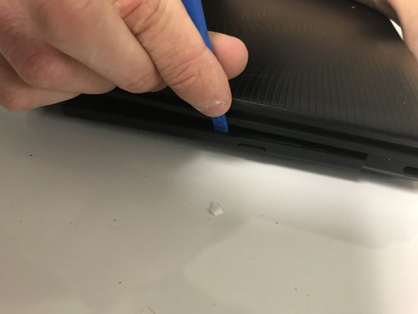 Use a plastic opening tool to remove the disk drive cover on the right side of the laptop.