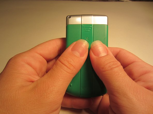 Place your thumbs on the pack of the phone and slide them in a downward motion to remove the cover.