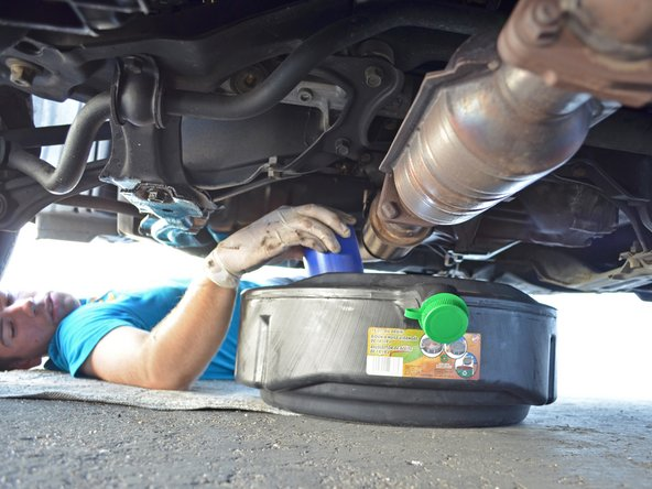 Image 3/3: If the oil filter is too tight to remove by hand, use an oil filter wrench to loosen it about 3/4 of a turn.