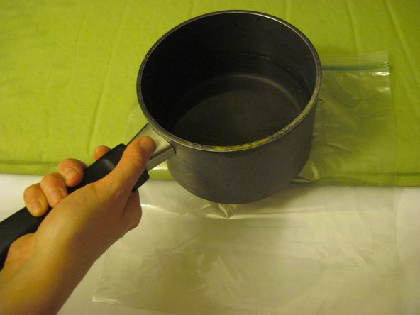 Image 3/3: Place the pan of hot water on top of the plastic layer and patch for one minute.