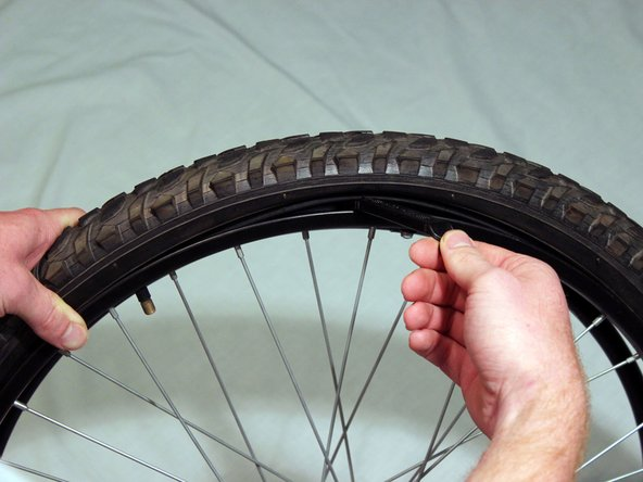 Take a tire lever and fit it under the edge of the tire.