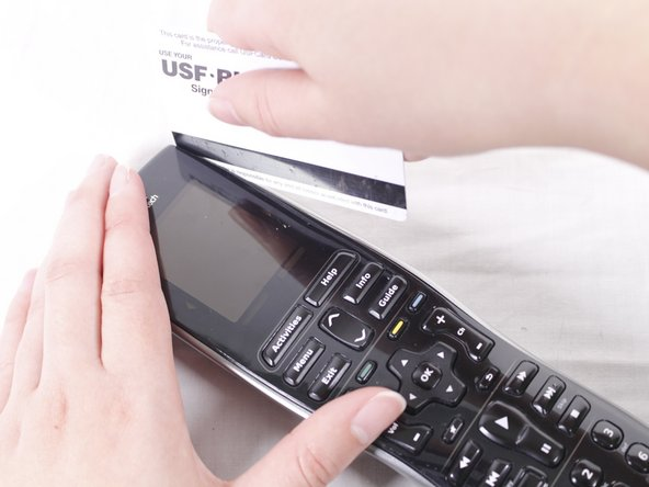 Pry the black, front face of the remote from the back silver part by inserting a credit card in between and sliding down.