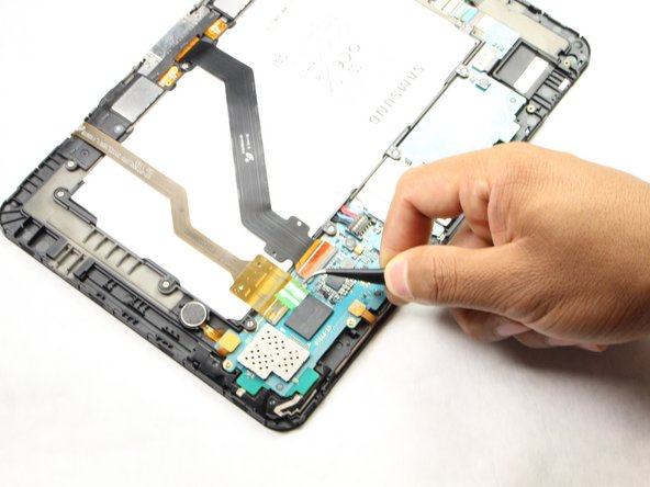 Using tweezers, peel away the green tape located on top of the two flexible ribbon cables.