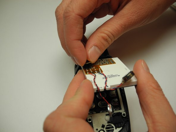 Image 2/3: Use your fingernail to detach the ribbon connecting the board to the screen.