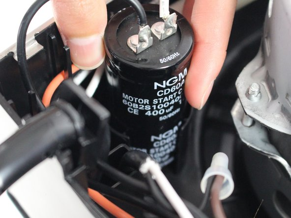 Lift the capacitor out of the plastic casing by pulling up.