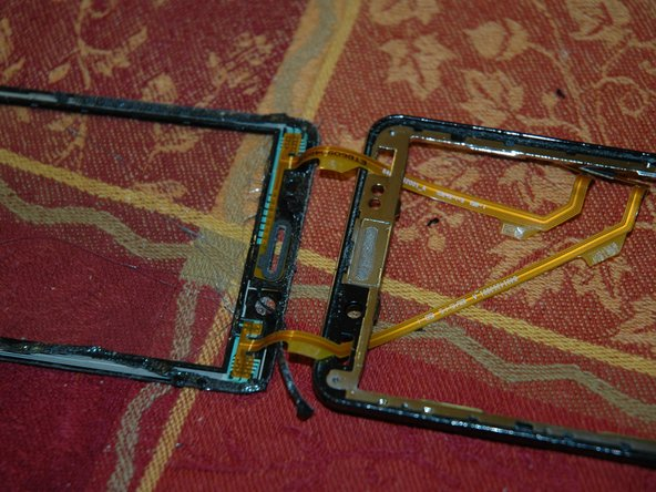 Slip the new glass/digitizer's two ribbon cables through the holes in the frame and stick the new glass to the frame.