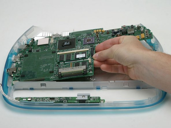Grasp the logic board to the left of where the optical drive used to be and pull it up from the lower case.
