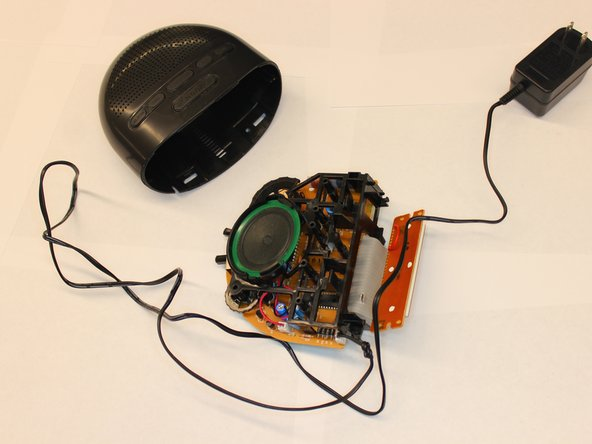 The PCB is supported by a plastic chassis. Grab the the plastic chassis with one hand while applying pressure to both sides of the alarm clock housing with the other hand.