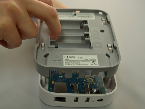 Once all five screws are removed, split the casing apart by applying gentle upwards pressure against the positive terminals in the battery compartment.