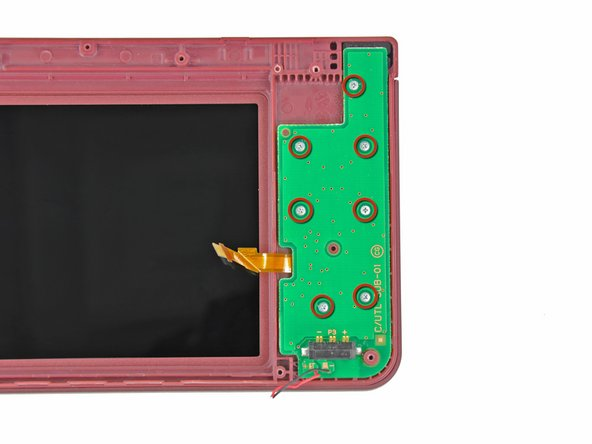 Ensuring that the upper LCD does not fall out of the front bezel, turn the DSi XL over.