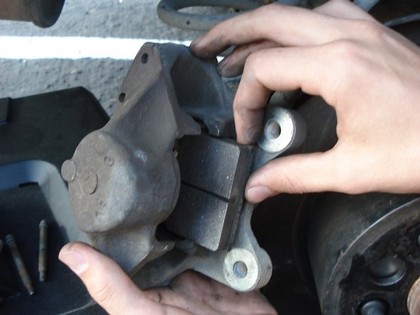 Remove both rear brake pads by pulling them out of calipers.