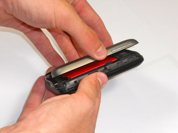 Remove back cover by applying pressure and sliding up towards the top of the phone.