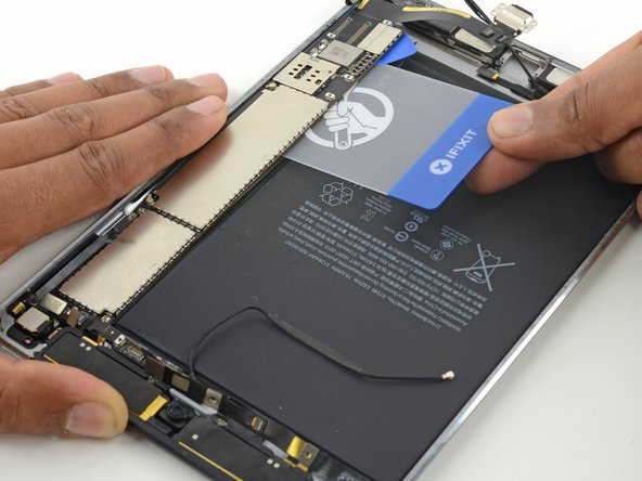 Image 1/2: Slide the plastic card under the logic board, toward the top of the iPad, near the cameras.