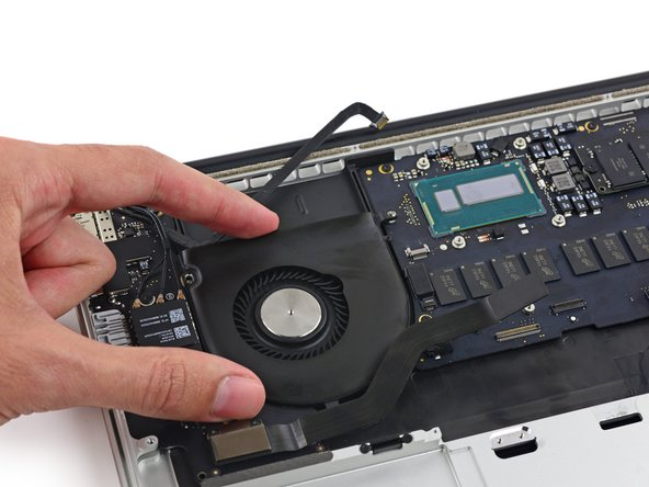 Lift the end of the fan from the heat sink cavity and pull it up and out toward the hinge of the laptop to remove it.