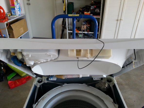 I used an old coat hanger to suspend the plastic cover out of the way by hooking it onto the trolley that I used to move the washing machine. This gives you access to the 4 rubber straps and 4 suspension rods.