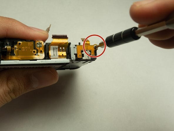 Remove the 3mm Phillips #000 screw located at the top right of the USB port.