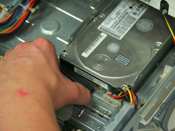 Entferne das Flachbandkabel sowie das Stromkabel von der Festplatte.