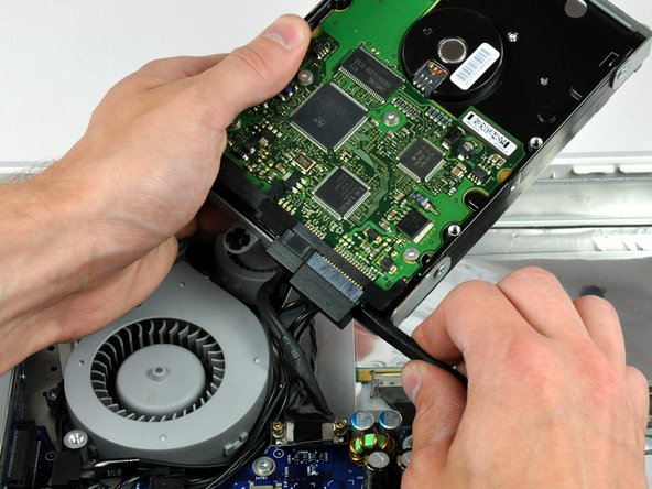 Insert the flat end of a spudger between the SATA power cable connector and the body of the hard drive.
