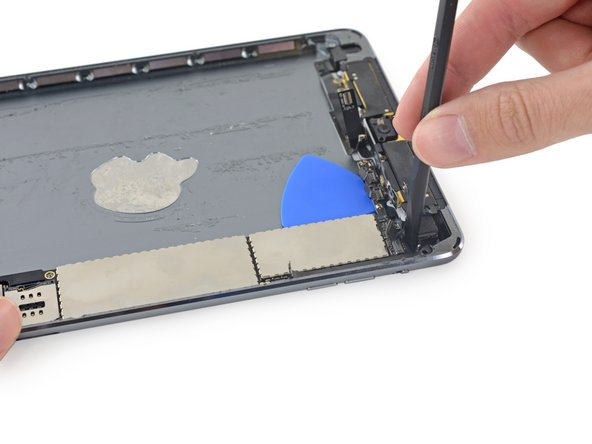 Carefully insert the flat end of a spudger between the rear-facing camera and the top of the logic board.