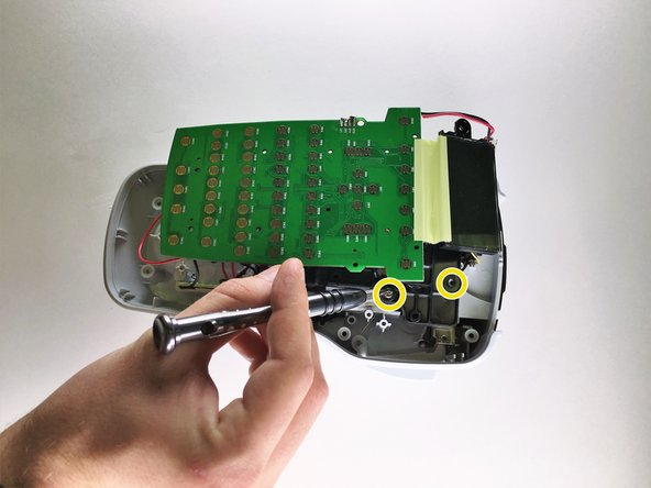 Lifting the circuit board, use a Phillips head screwdriver to remove the two 1.2mm Phillips #1 screws from under the circuit board.