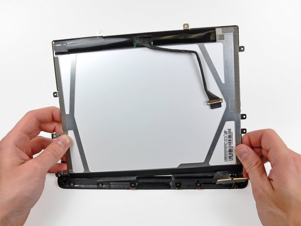 Image 2/2: Carefully peel the adhesive securing the long side of the LCD to the display frame, then remove the LCD.
