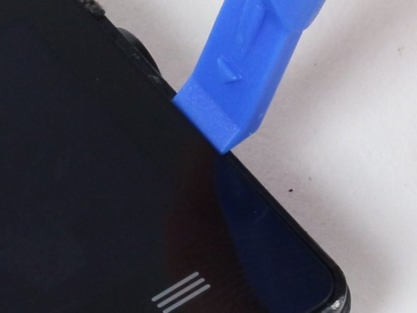 Place the blue plastic opening tool in-between the screen and plastic casing of the watch and slowly pry up one side of the screen.