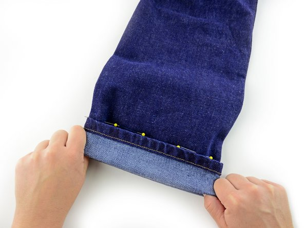 Image 1/3: Insert a row of pins perpendicular to the bottom of the cuff, catching the fold and holding it in place.