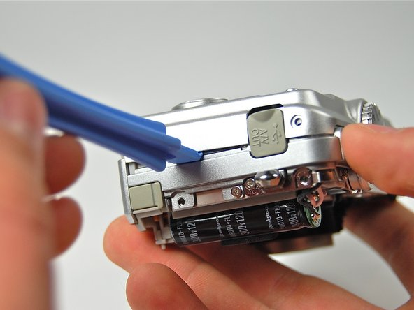 Using the plastic opening tool pry the back casing of the camera.