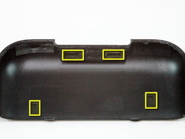 This image shows the two tabs and two catches located on the underside of the antenna cover. The two tabs at the top of the image must be pushed towards the black cover to release them.
