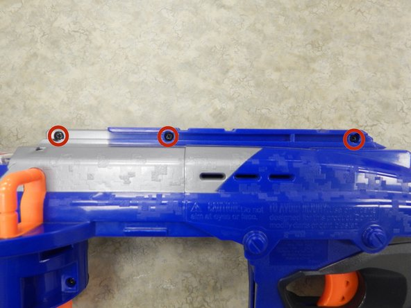 Remove the three 9.0 mm Phillips screws holding the top latch of the Nerf Gun together.