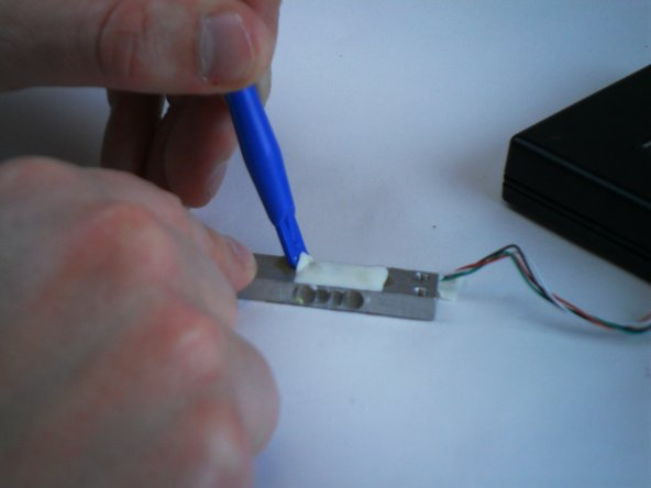 With the sensor detached, use a plastic opening tool to peel away the glue holding the wires.