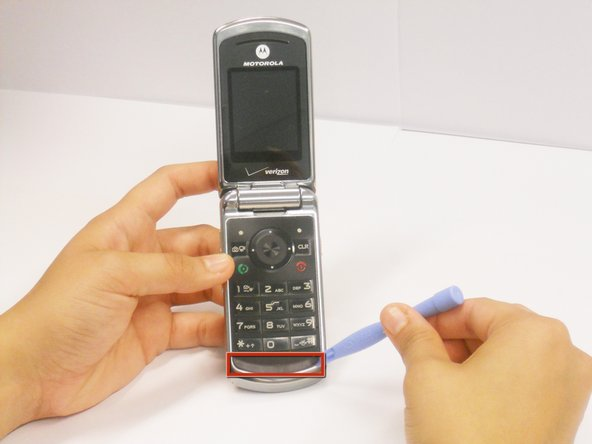 Using a plastic opening tool, carefully peel back the rubber strip located at the bottom of the keypad