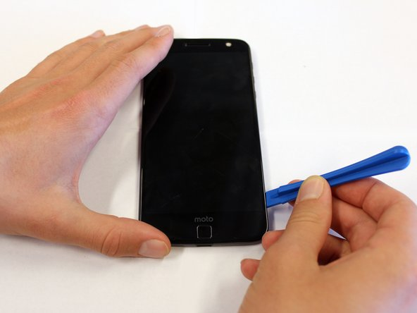 Slide the opening tool around the edge of the screen to loosen the adhesive.