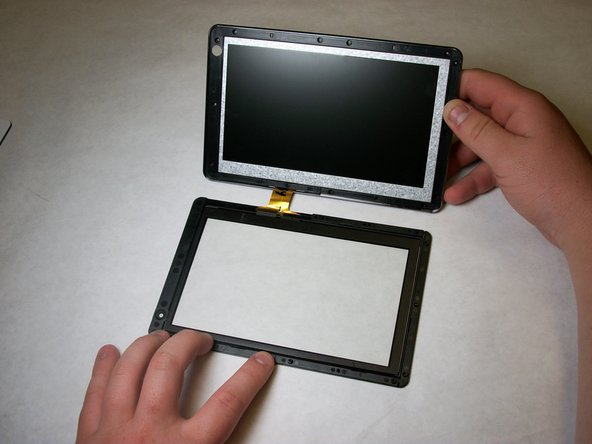 Once the glass and display have been separated, pull the glass away from the display and carefully slide the ribbon cable out of the display housing.