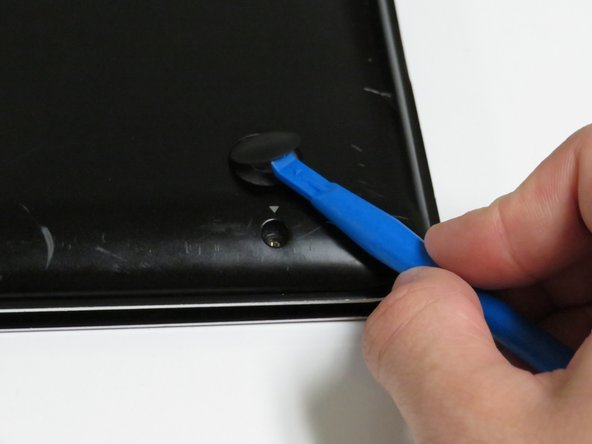 Locate the rubber feet at every corner of the laptop back panel. Use the ifixit prying tool, and break the adhesive between the rubber feet, and the case.