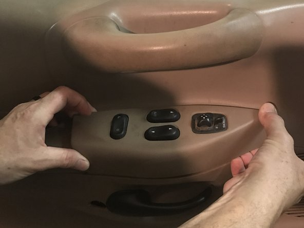 Grasp the window button housing and squeeze while lifting up and away from the door.
