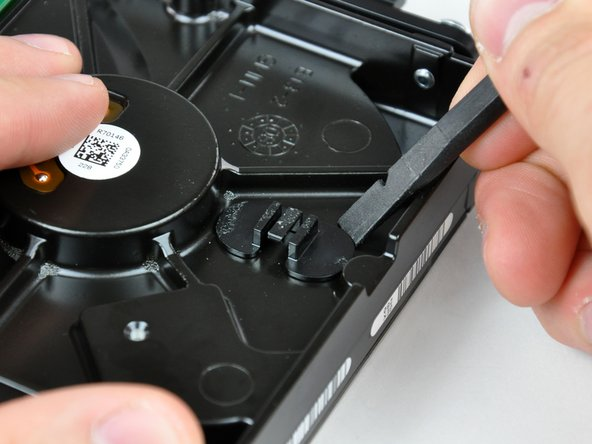 Use the flat end of a spudger to pry the thermal sensor bracket off the face of the hard drive.