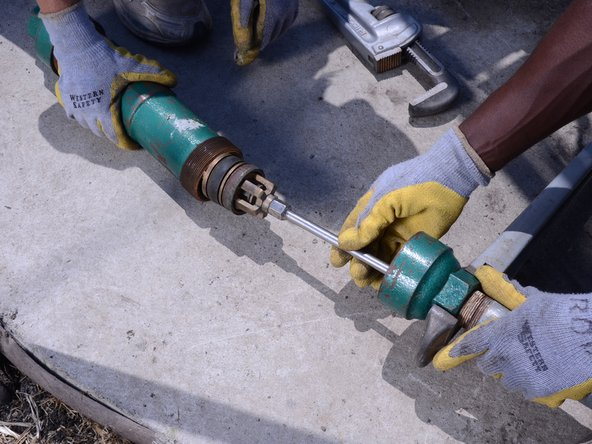 Slowly pull the cylinder off of the pump rod, exposing the traveling valve and foot valve.