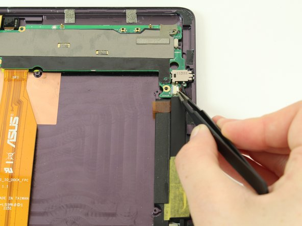 Using tweezers, pull the black part of the connection between the mother board and speakers out of the white part of the connection.