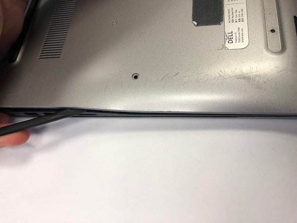 Using the flat head side of the spudger separate the the back panel from the rest of the laptop.