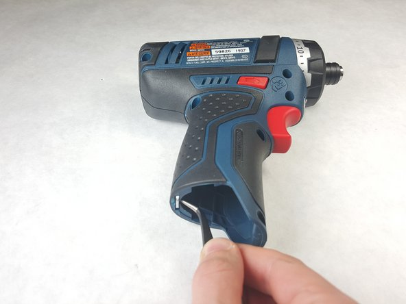 Image 2/2: Place the tweezers in the groove on the inside of the clip. The clip is firmly placed, so this will take some effort. Use your other hand to brace the drill and pull downward until the clip comes loose.